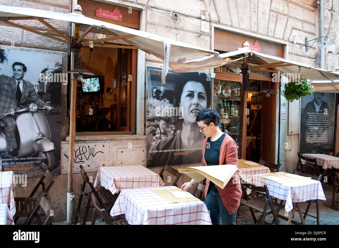 Waitress laying tables Restaurant  Campo de' Fiori district, with Anna Magnani and Gregory Peck photographs, Rome, Italy - Stock Image