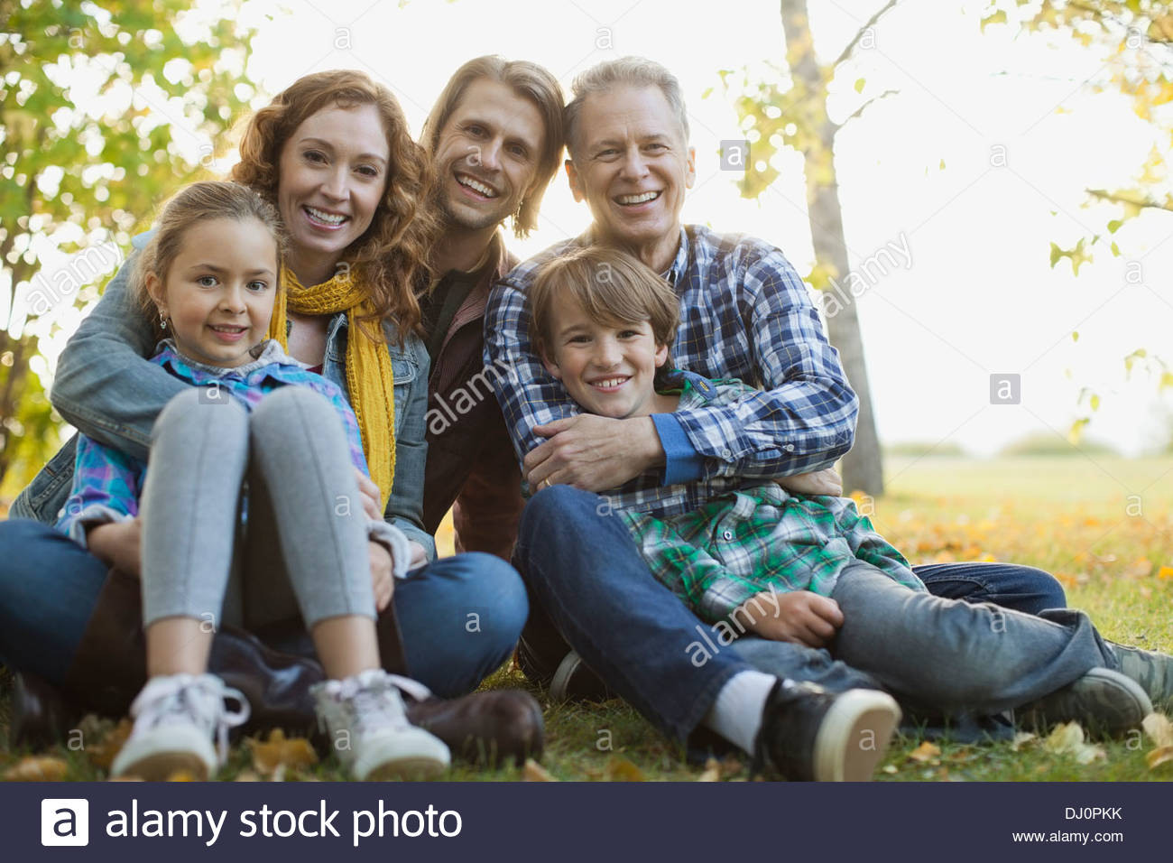 Portrait of loving multi-generation family sitting at park - Stock Image