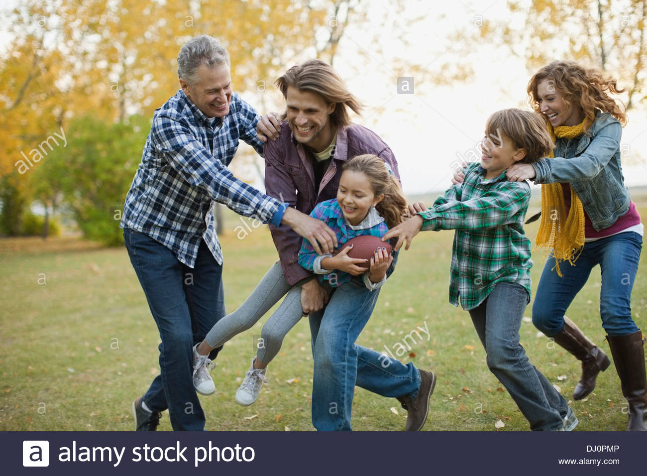 Happy multi-generation family playing American football in park - Stock Image