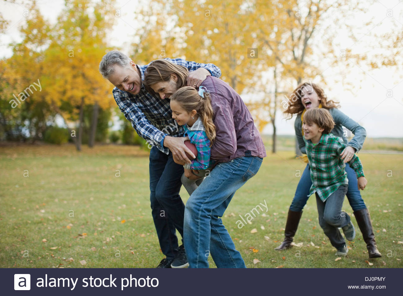 Multi-generation family playing American football in park - Stock Image