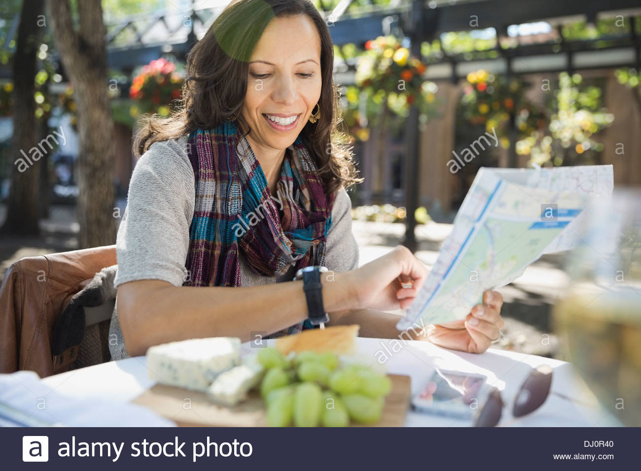 Woman with map checking time at outdoor cafe - Stock Image