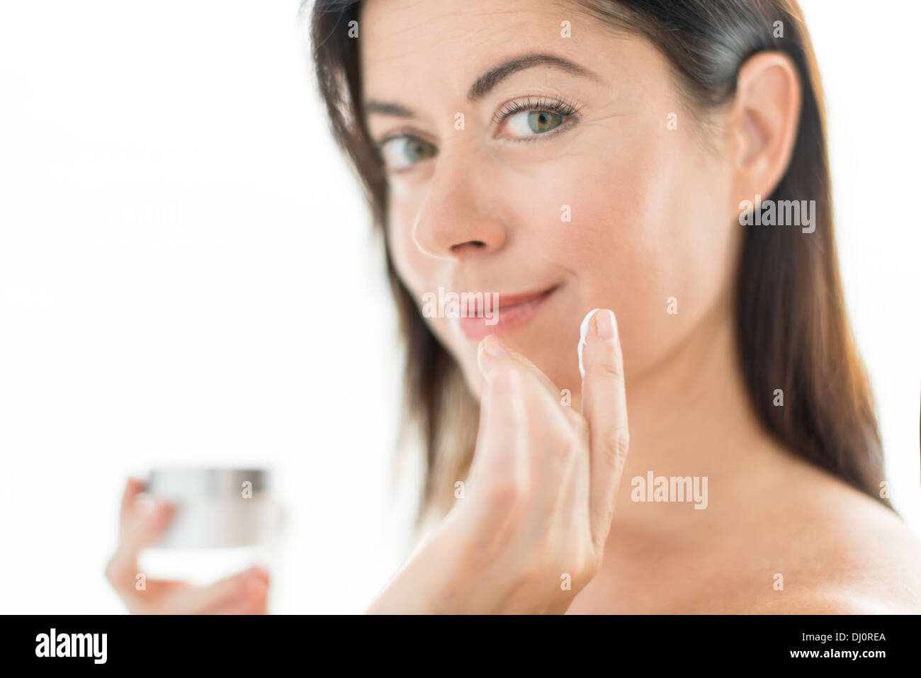 portrait of a beautiful mature lady preventing wrinkles by using a luxurious face lotion - Stock Image