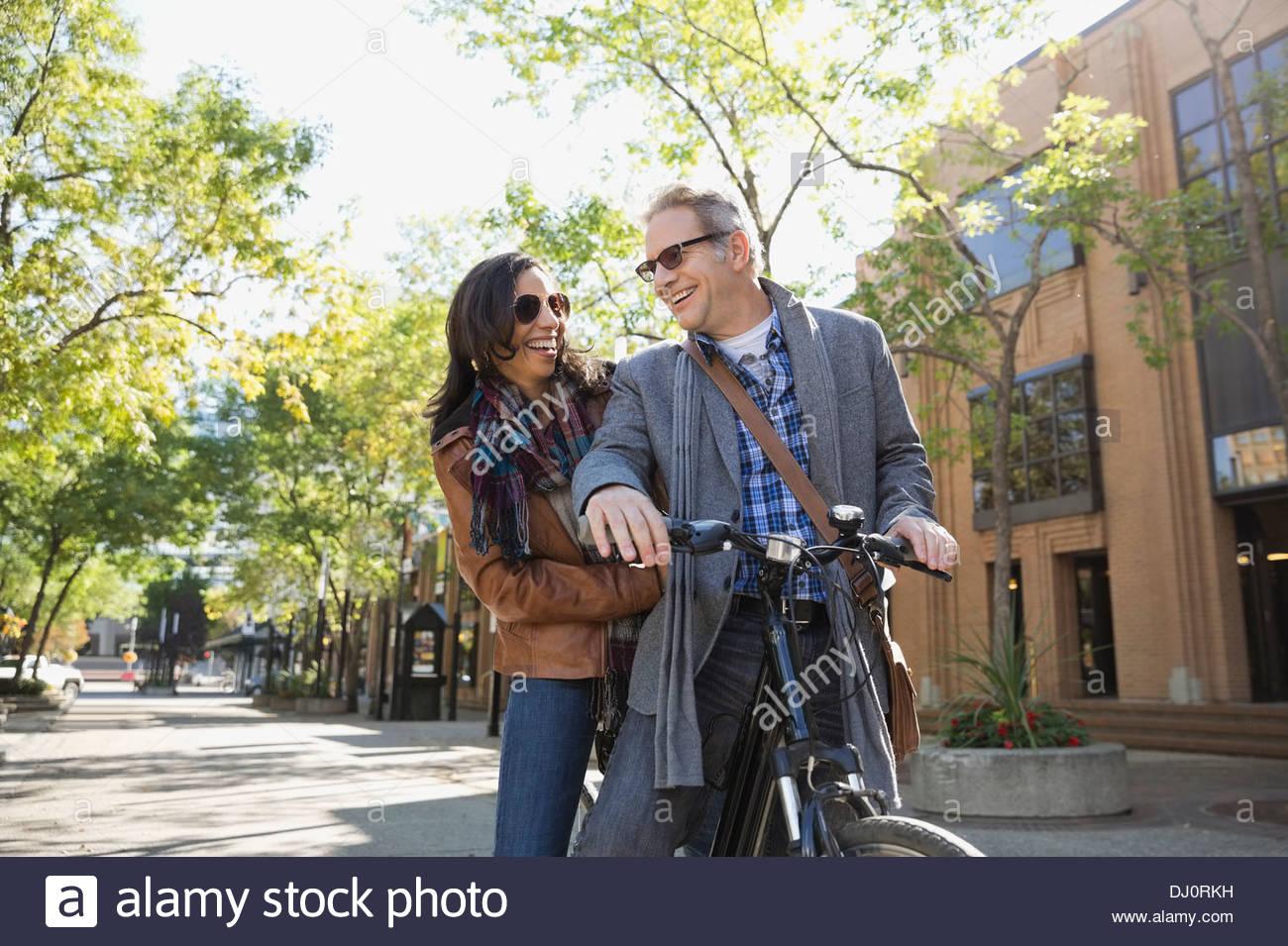 Smiling couple sitting on bicycle - Stock Image