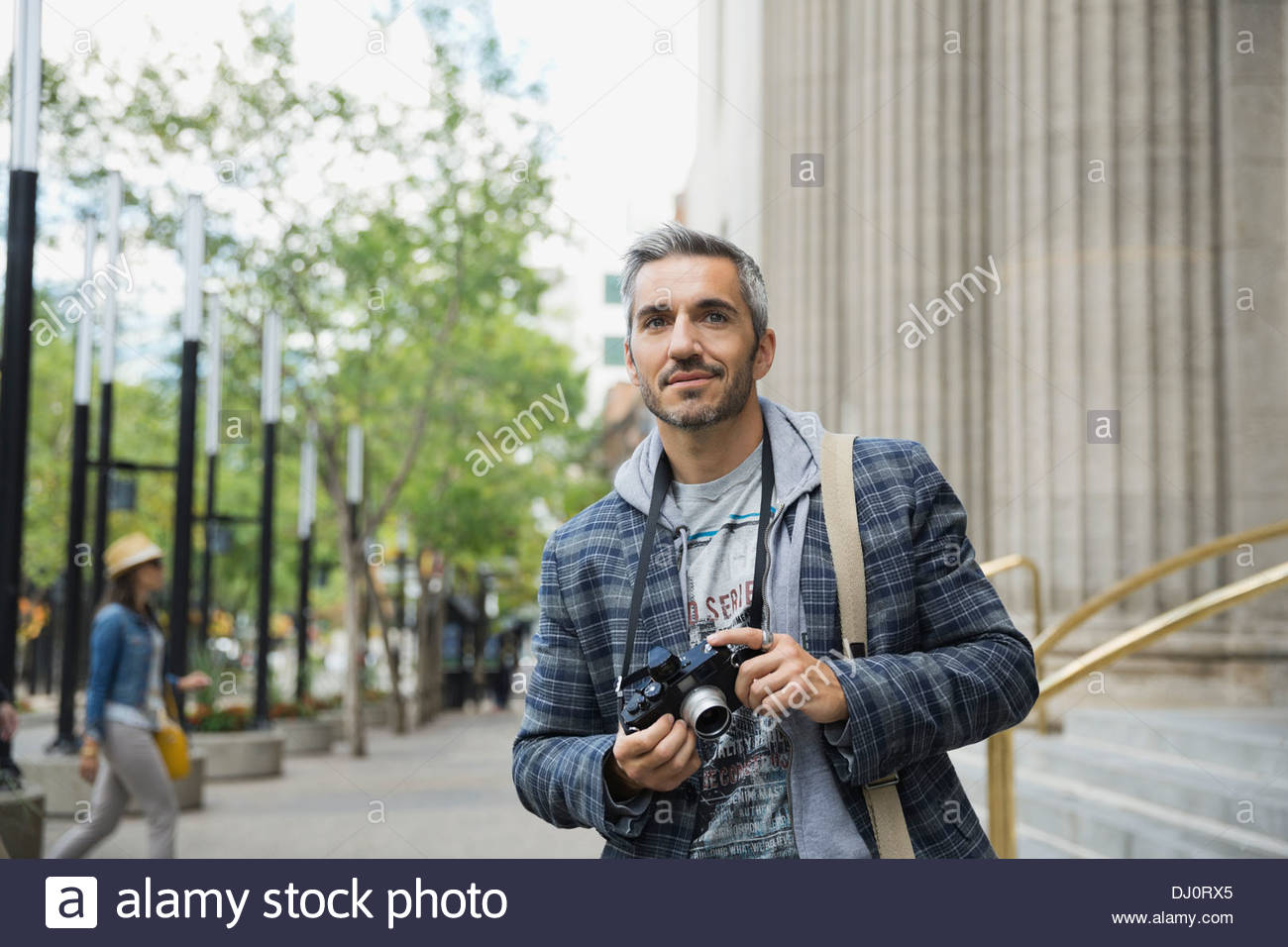 Thoughtful man with camera standing outdoors - Stock Image