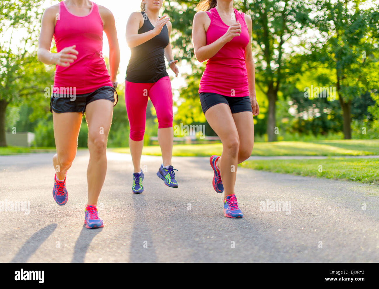 group of healthy girls running outdoors at sunset with lens flare. - Stock Image