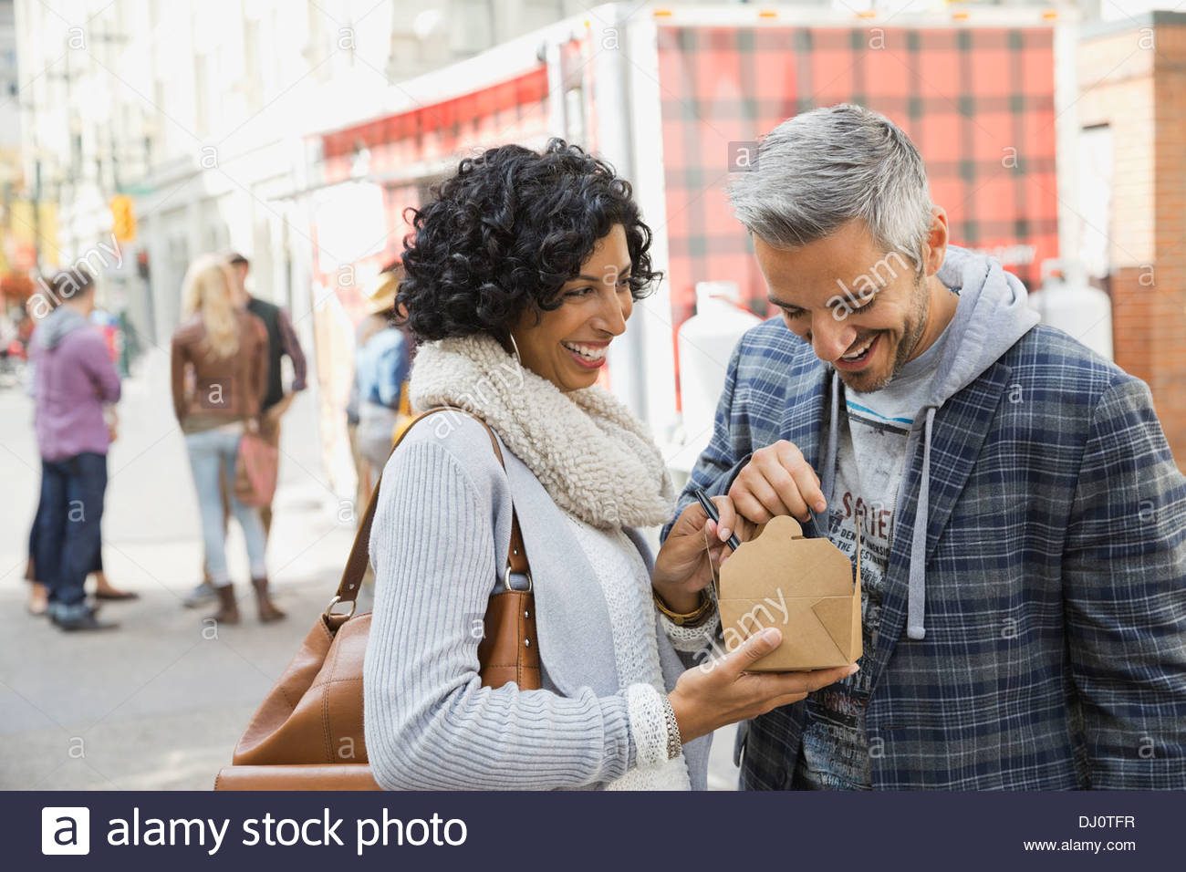 Happy couple enjoying fast food on city street - Stock Image