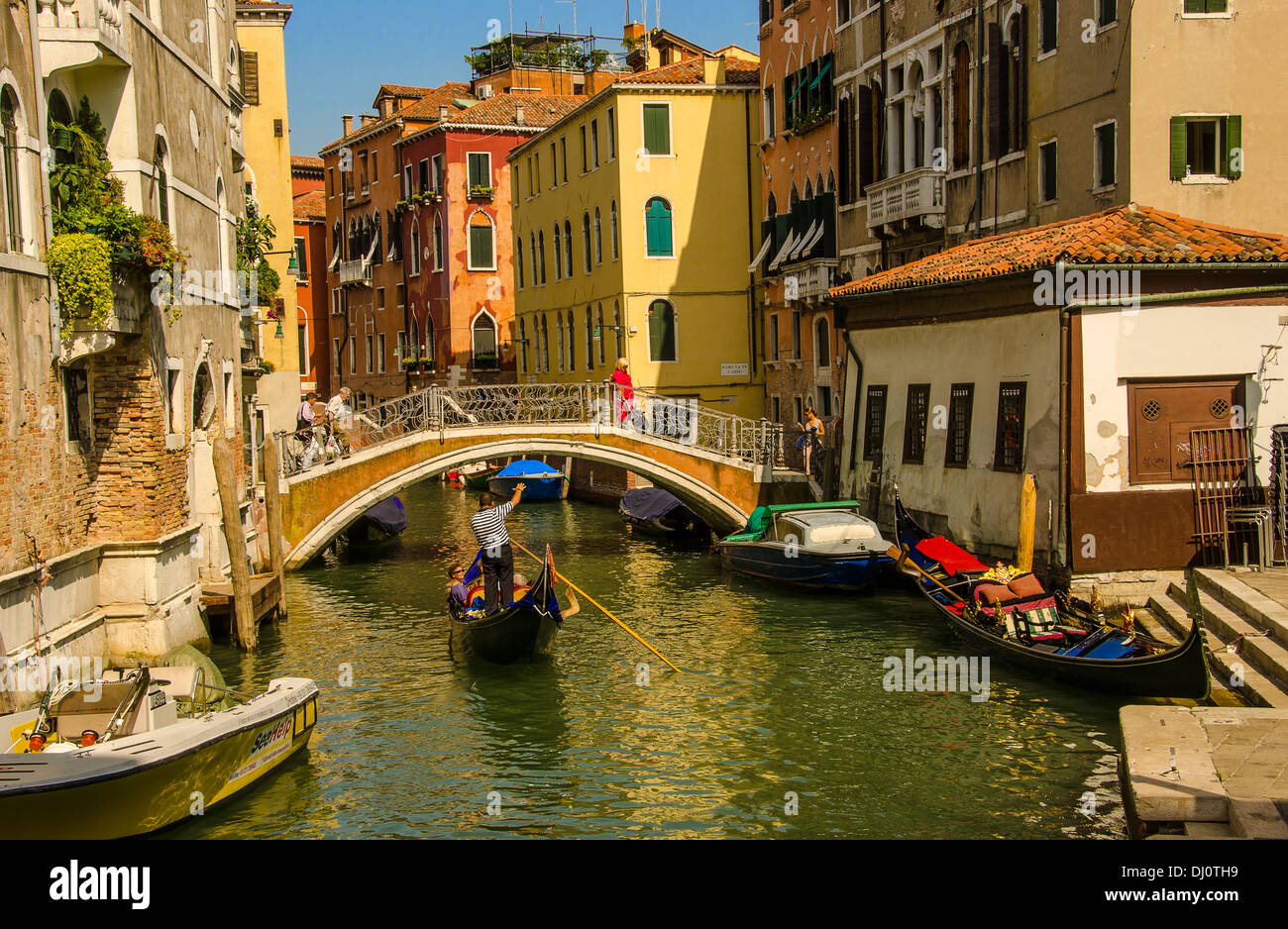 Gondolier taking passengers for an informative gondola ride in Venice, Italy. - Stock Image