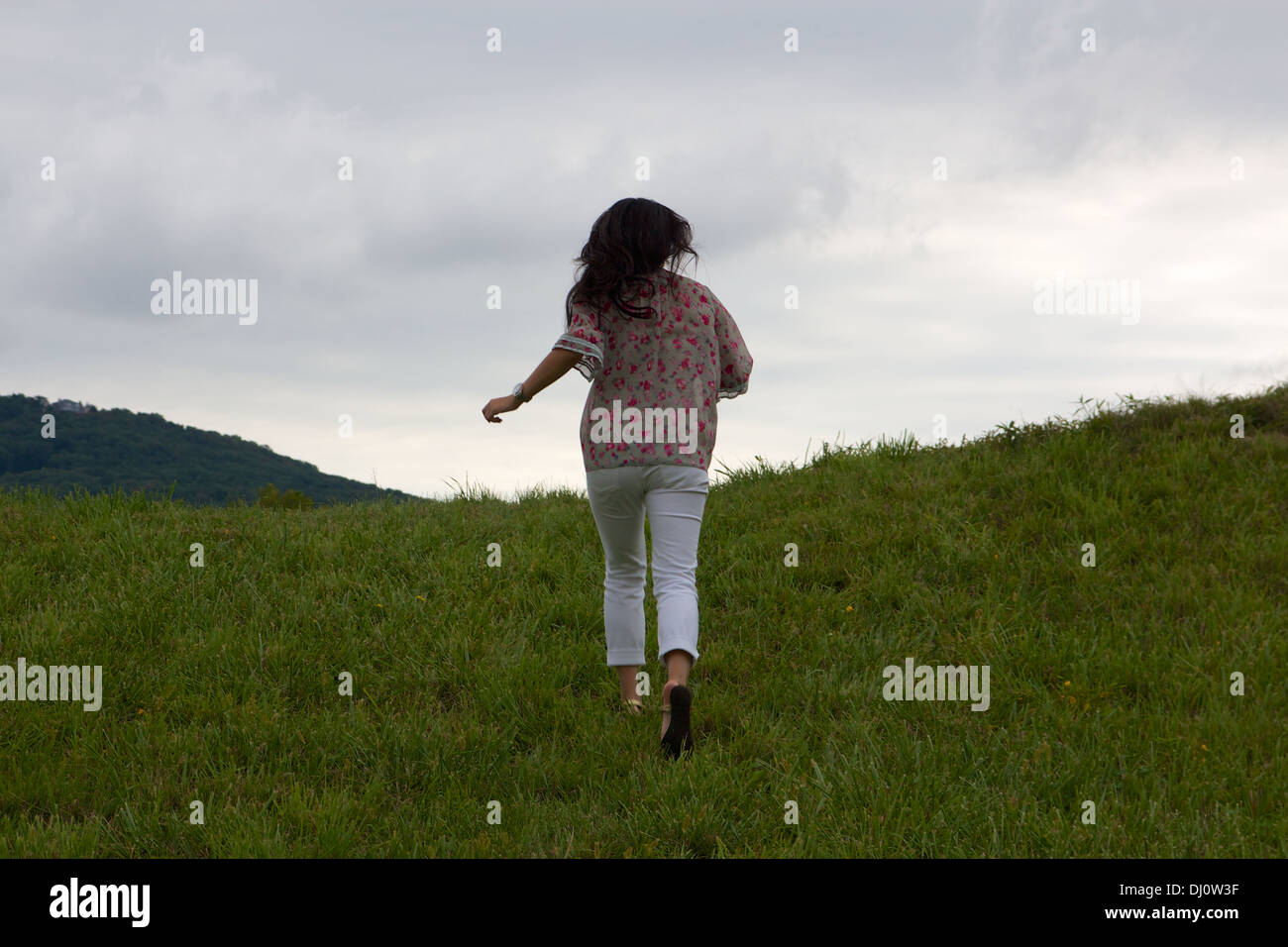Young Chinese woman seen from behind as she runs away from the camera up a green hill. Stock Photo