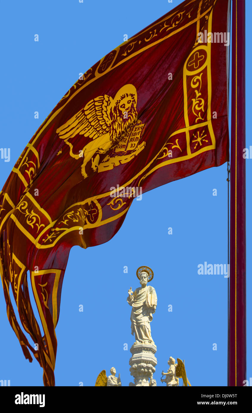 Statue of St Mark, at St. Mark's Cathedral in Venice with the Venetian flag in the foreground. Stock Photo