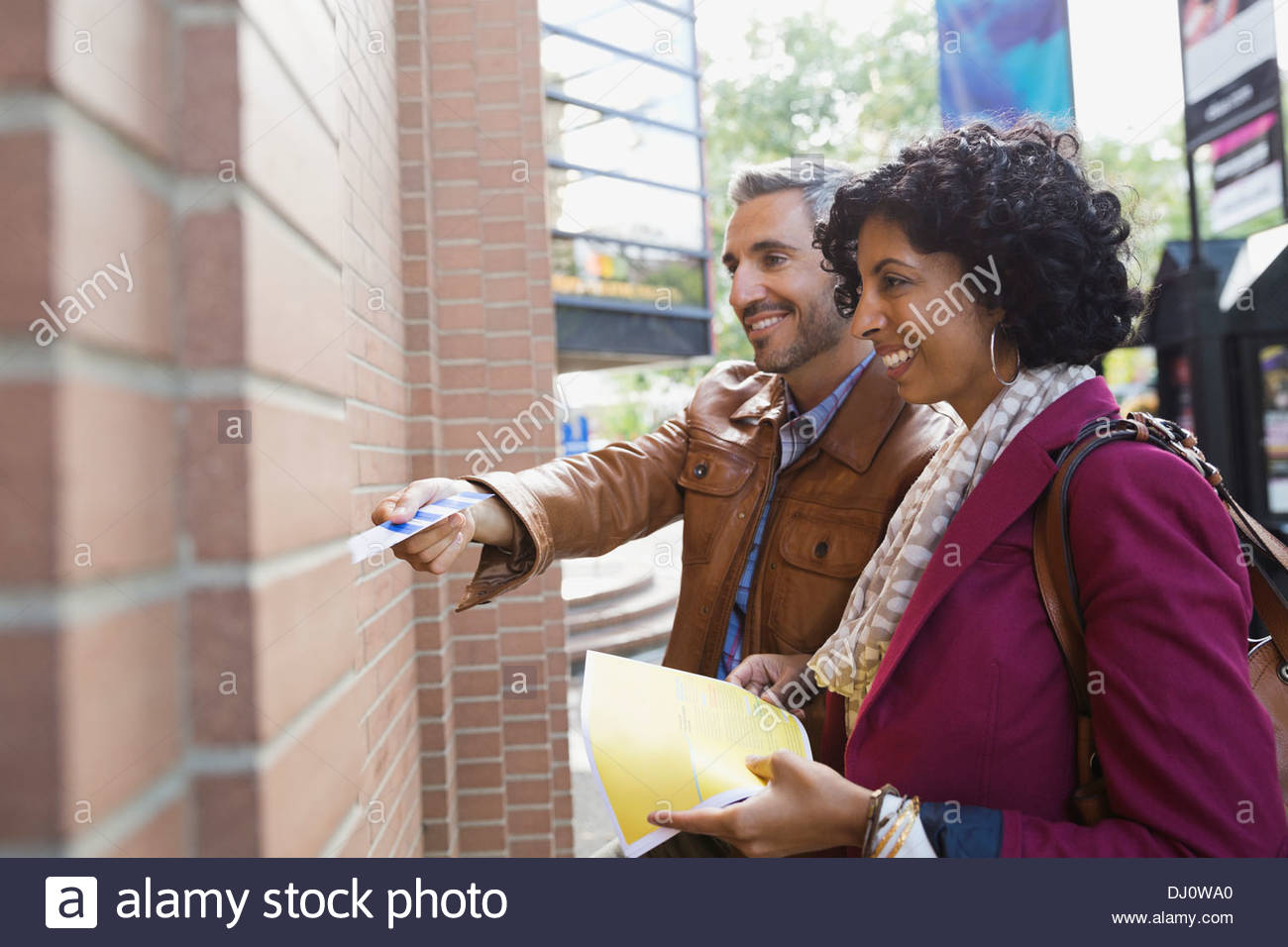 Couple handing tickets to attendant for show entry - Stock Image