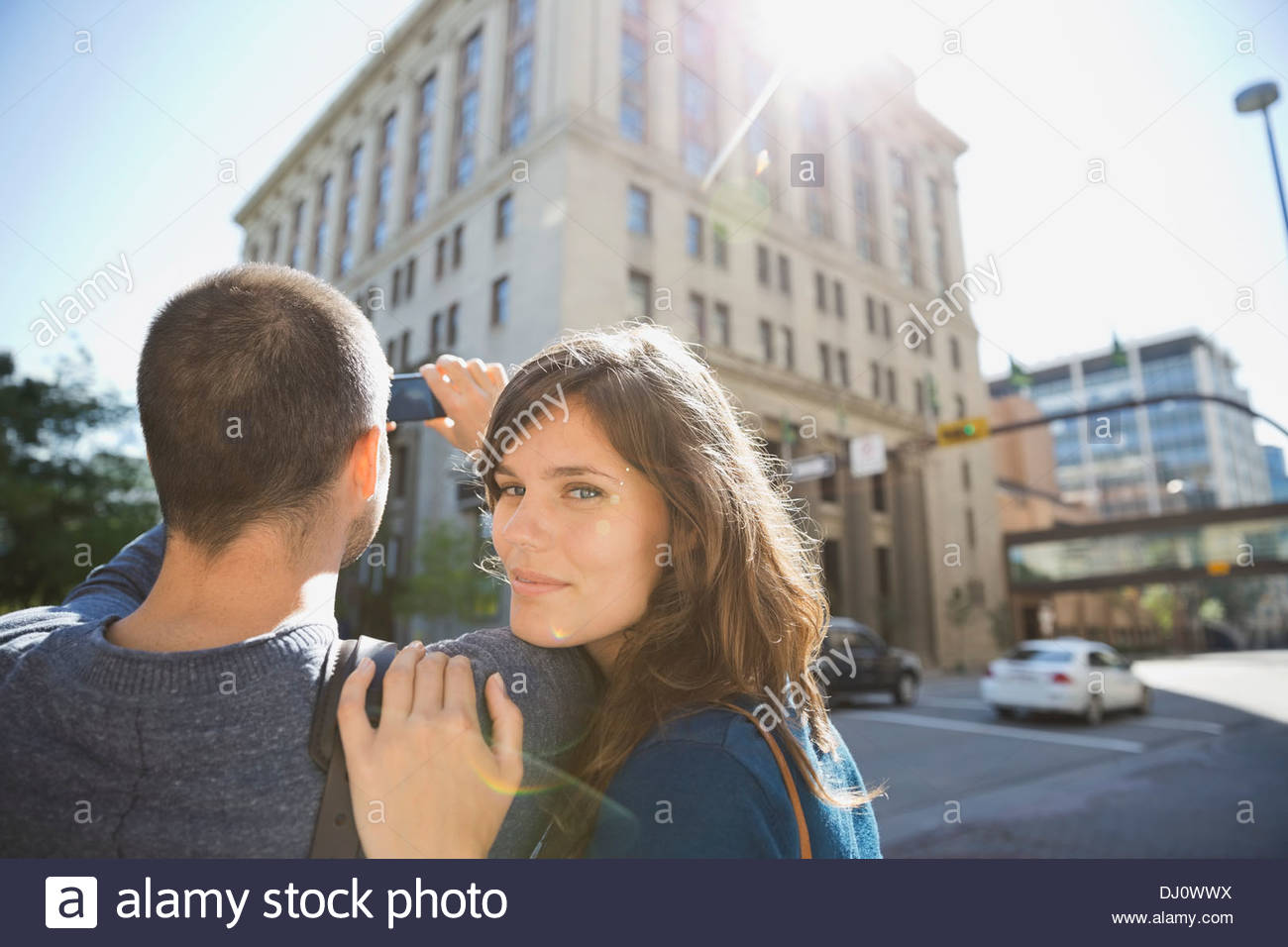 Portrait of woman with man photographing building - Stock Image