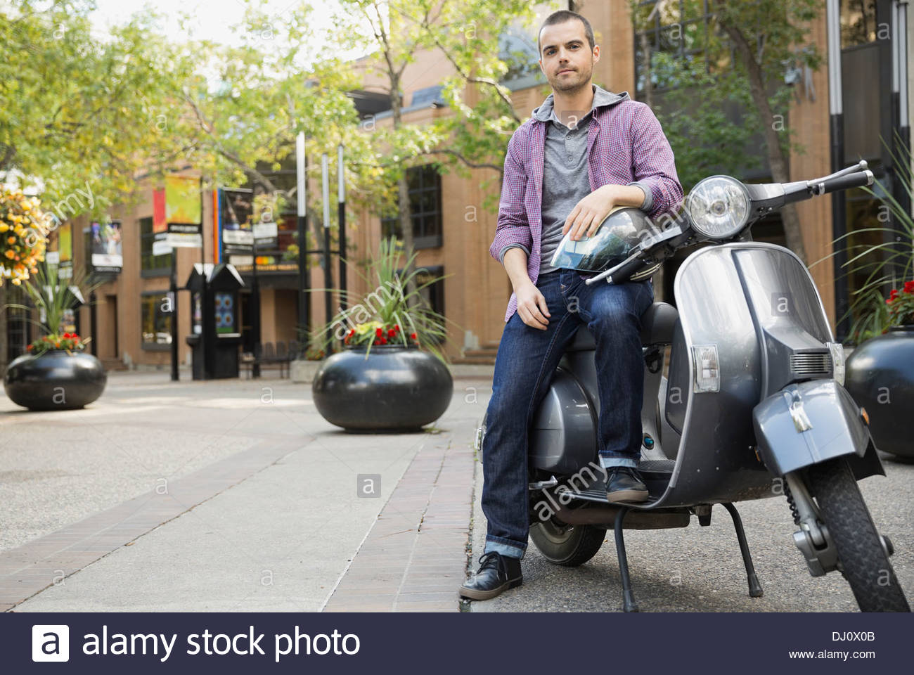 Portrait of man sitting on scooter - Stock Image