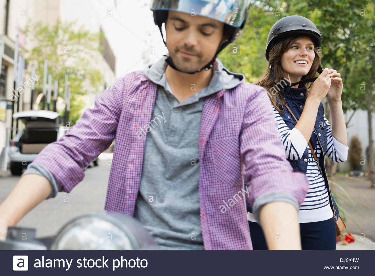 Couple getting onto scooter with helmets - Stock Image