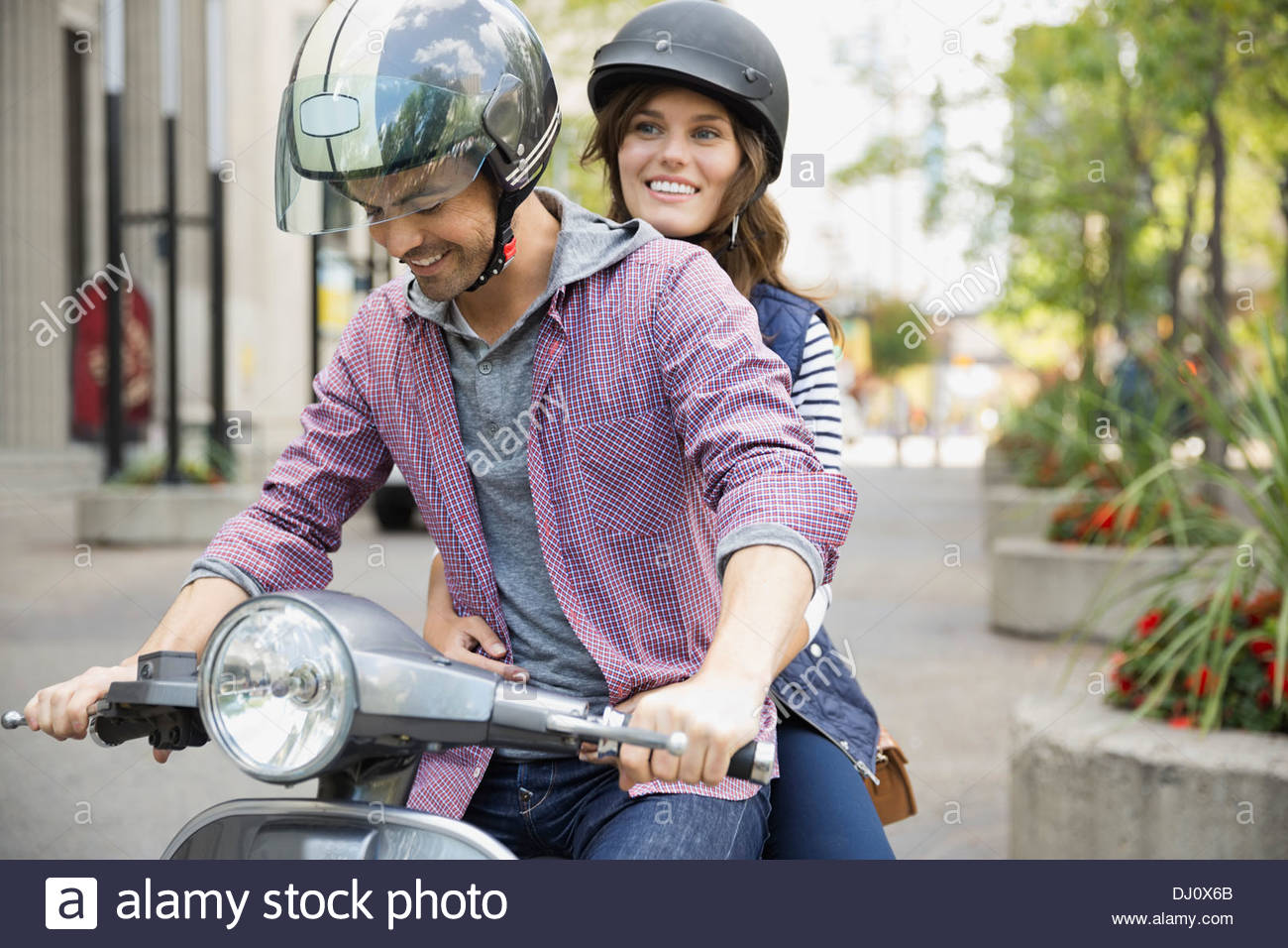 Couple riding scooter - Stock Image