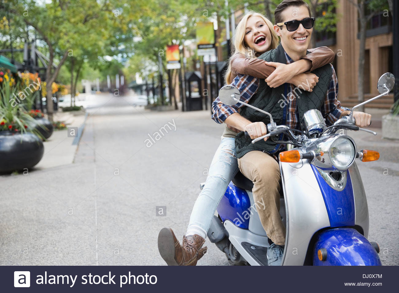 Couple riding on scooter - Stock Image