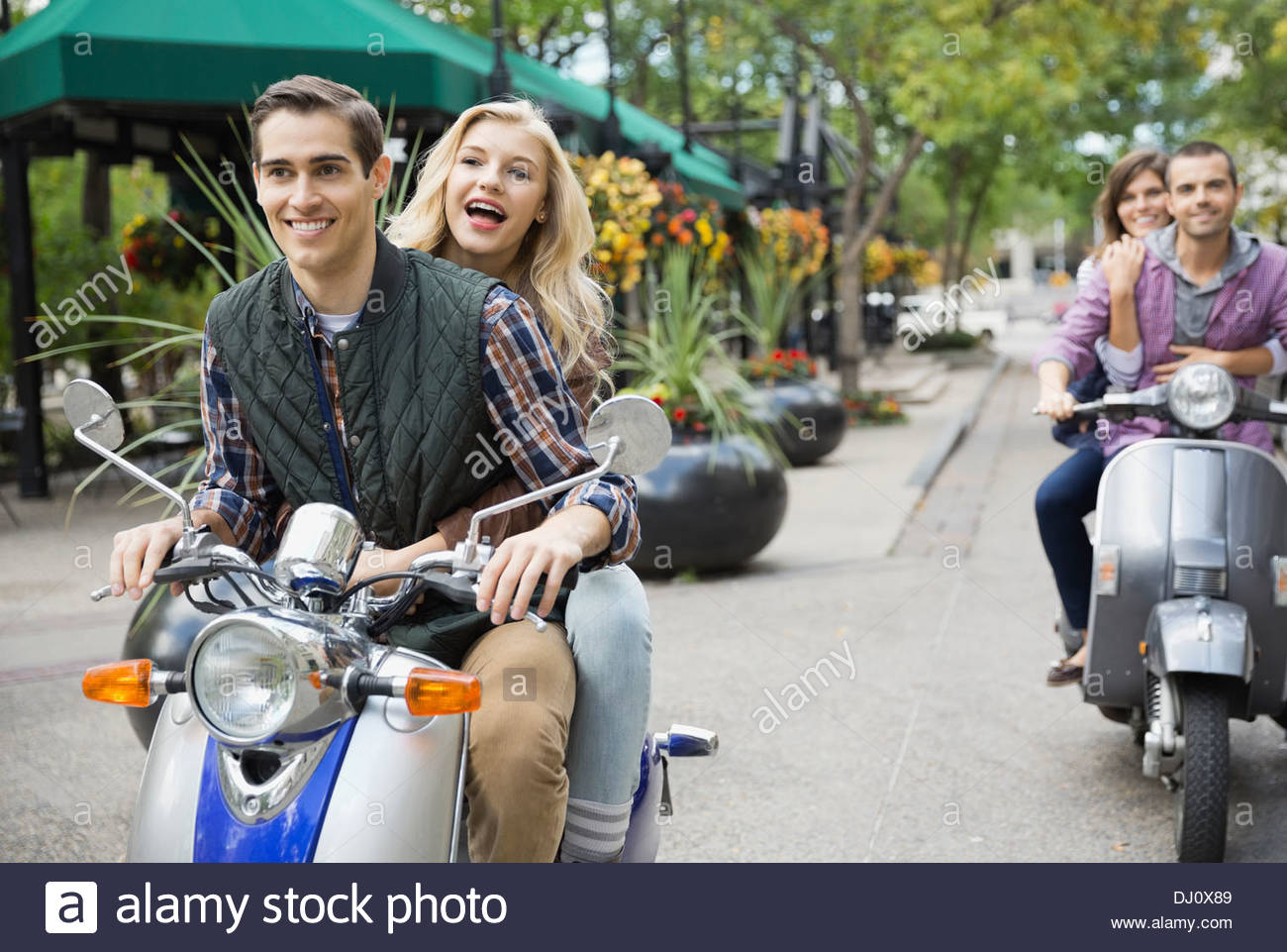 Two couples riding scooters on city street - Stock Image