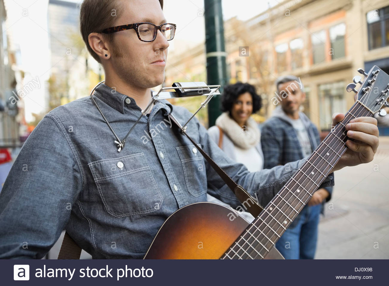 Street musician entertaining pedestrians - Stock Image
