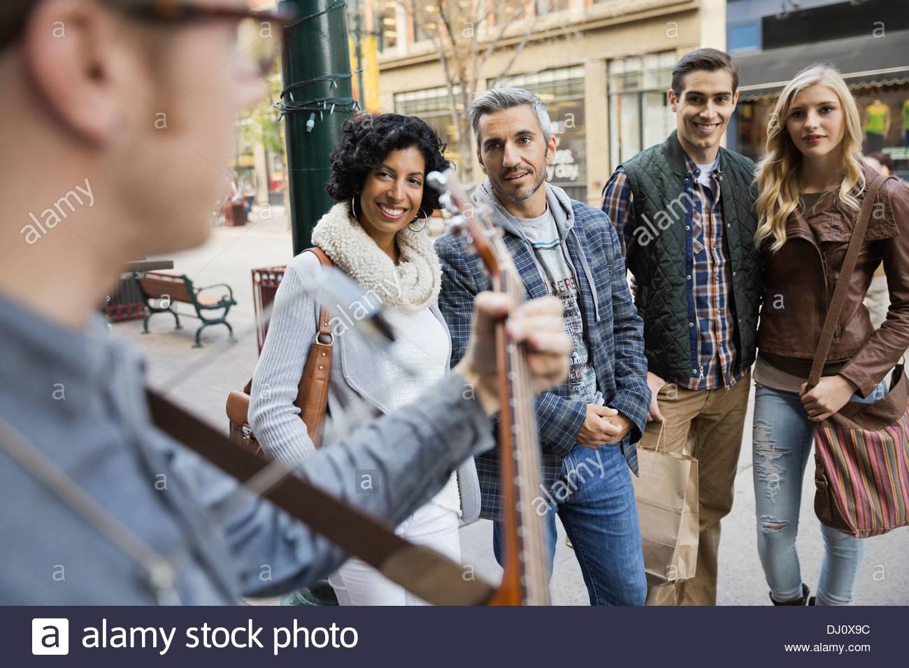 Pedestrians listening to street musician - Stock Image