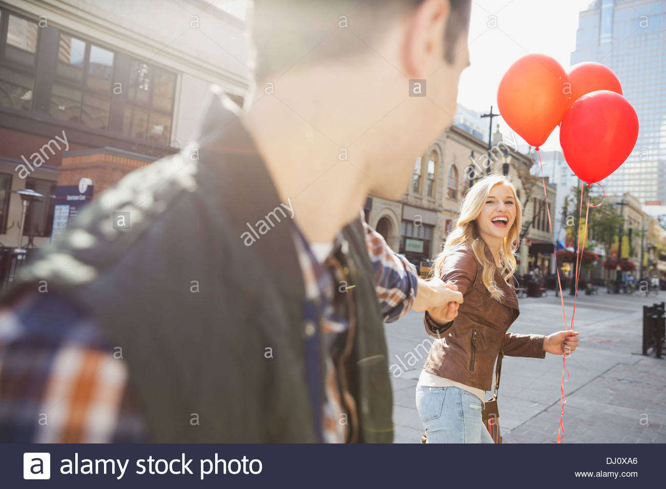 Smiling woman leading man down city street - Stock Image