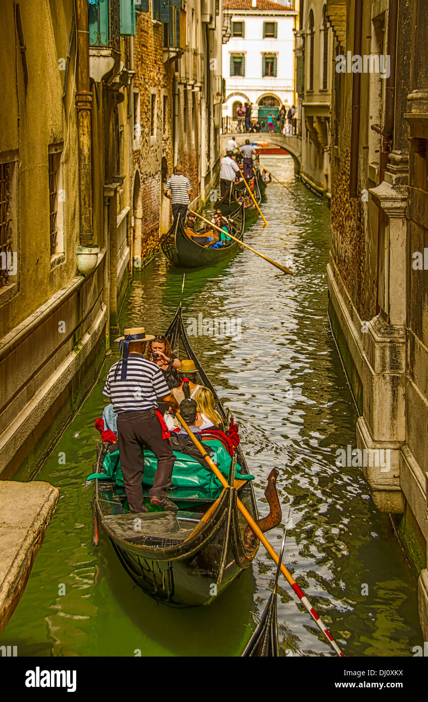 Gondola rides along a busy small canal in Venice, Italy - Stock Image