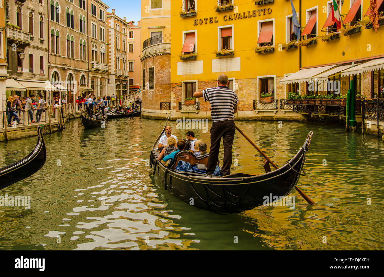 Gondolier setting out for a scenic tour of Venice canals. - Stock Image