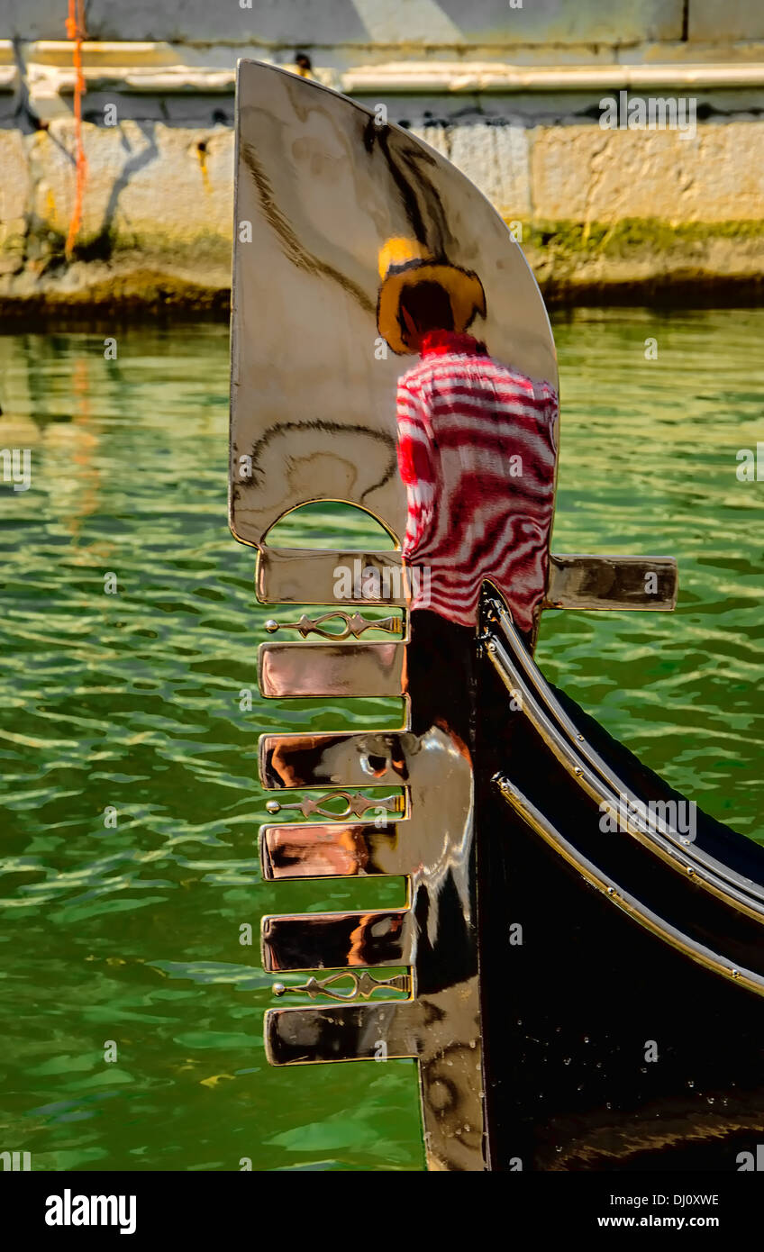 Reflection of a gondolier on the prow of his gondola. - Stock Image