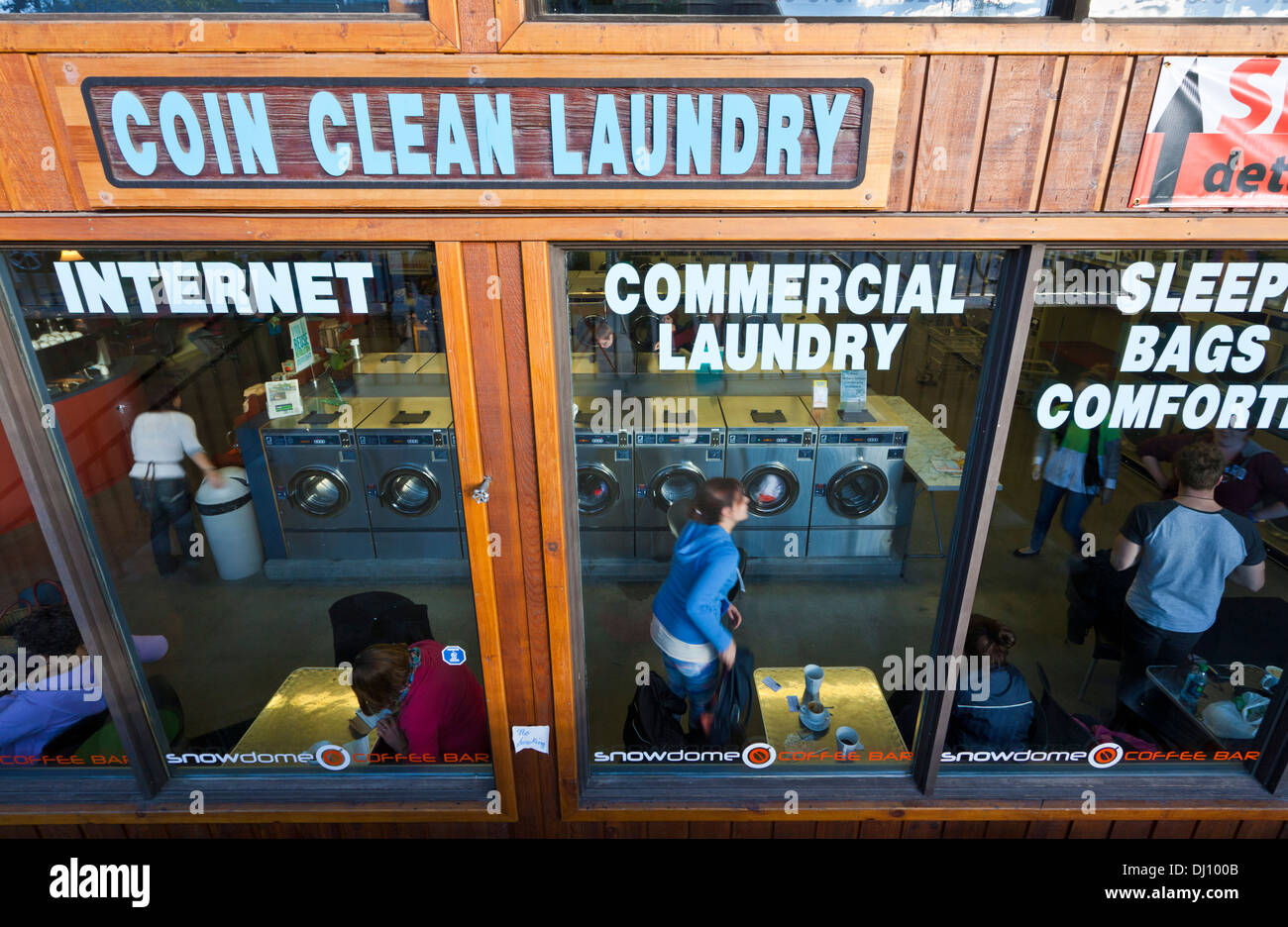 People in the Coin operated laundry laundrette laundromat doing their laundry in Jasper Alberta Canada - Stock Image