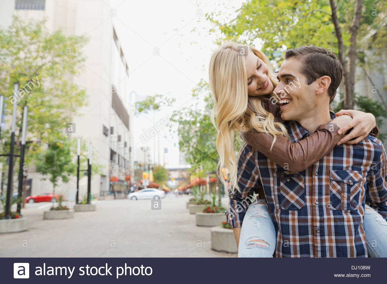 Playful couple walking on city street - Stock Image