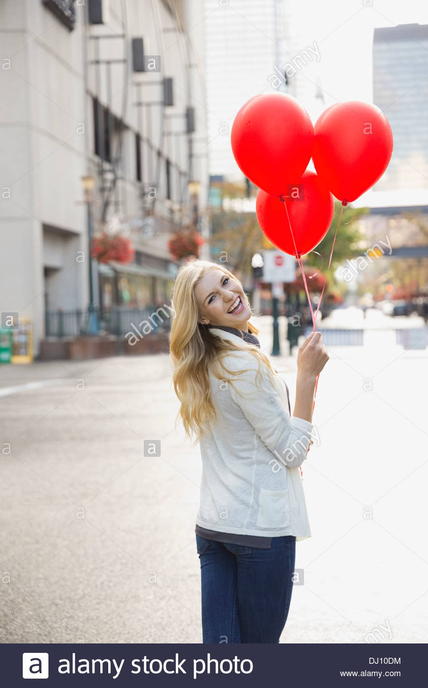 Woman standing on city street holding red balloons - Stock Image