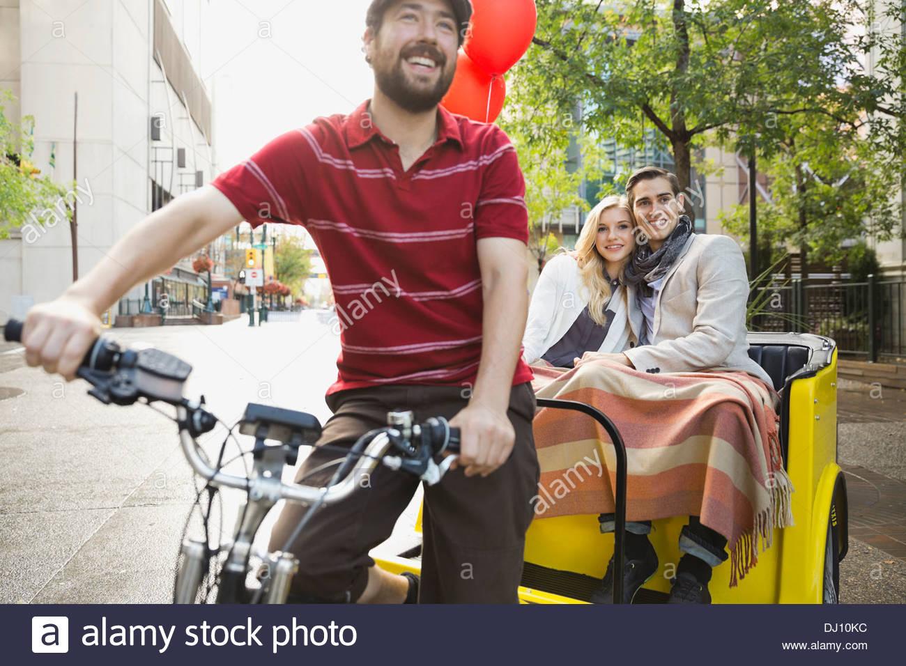 Rickshaw driver and couple on city street - Stock Image