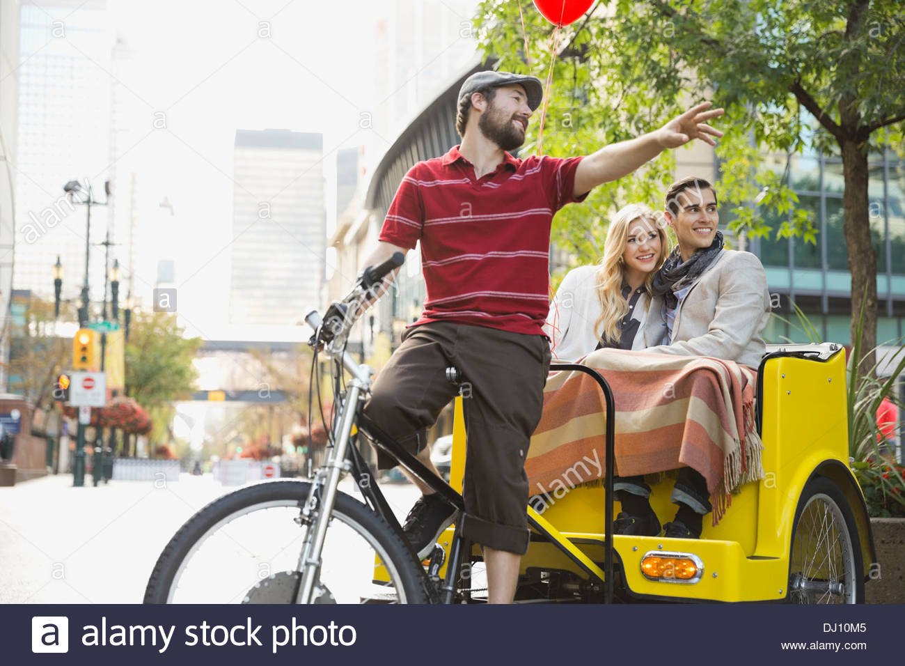 Rickshaw driver pointing out city landmarks to couple - Stock Image
