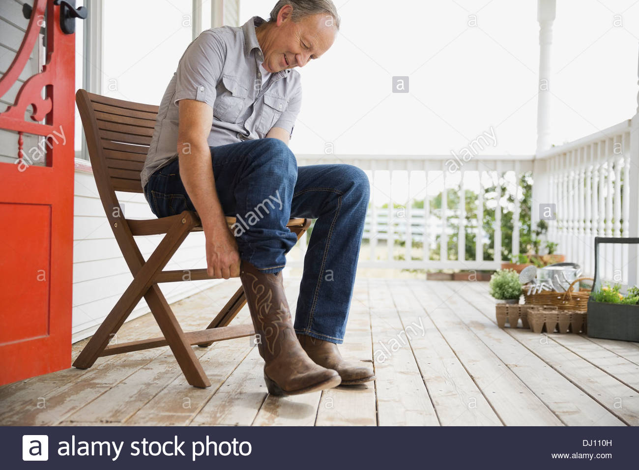 Man putting on cowboy boots - Stock Image