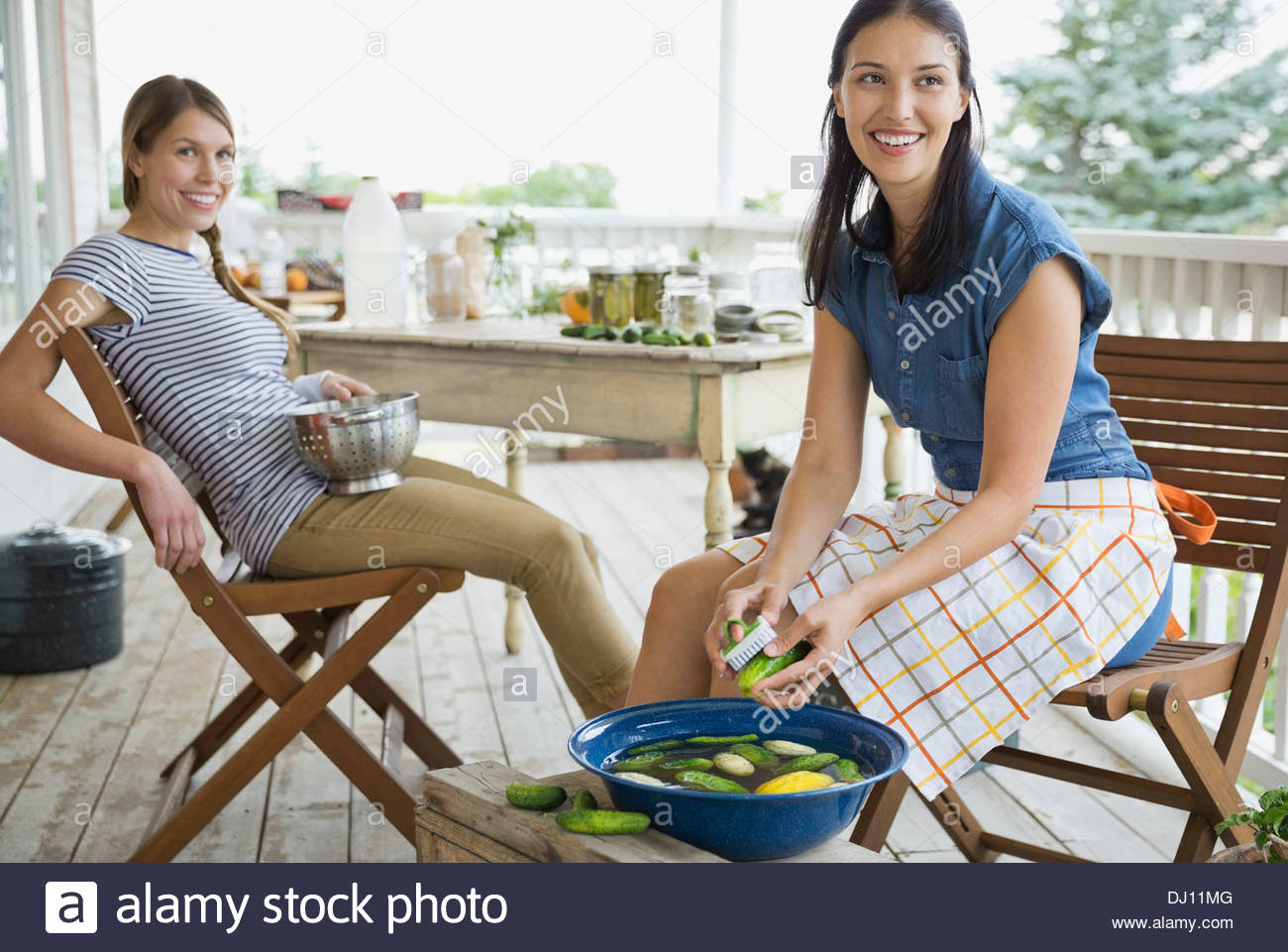 Women washing vegetables on porch - Stock Image