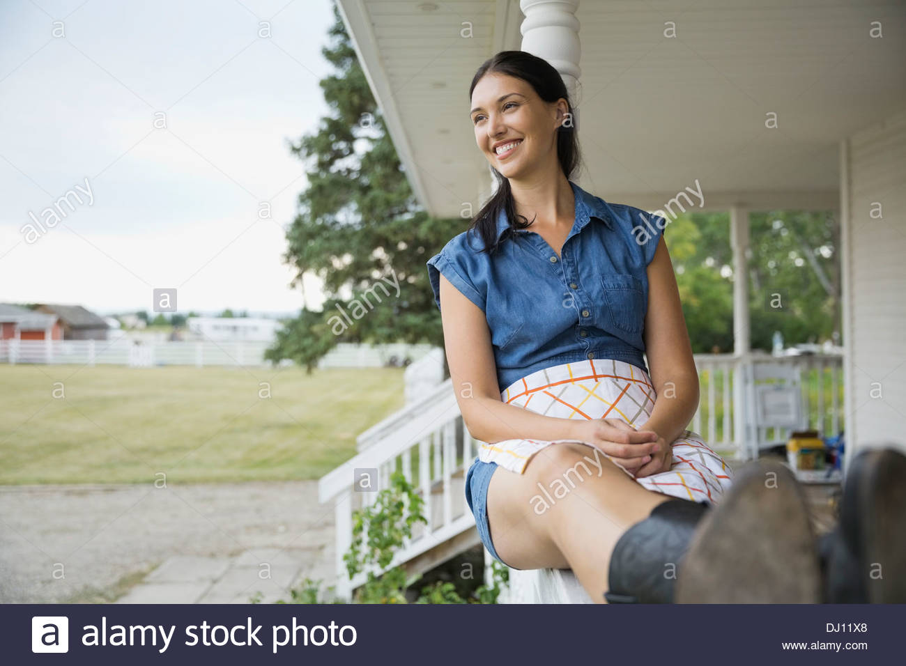 Smiling woman sitting on porch railing - Stock Image