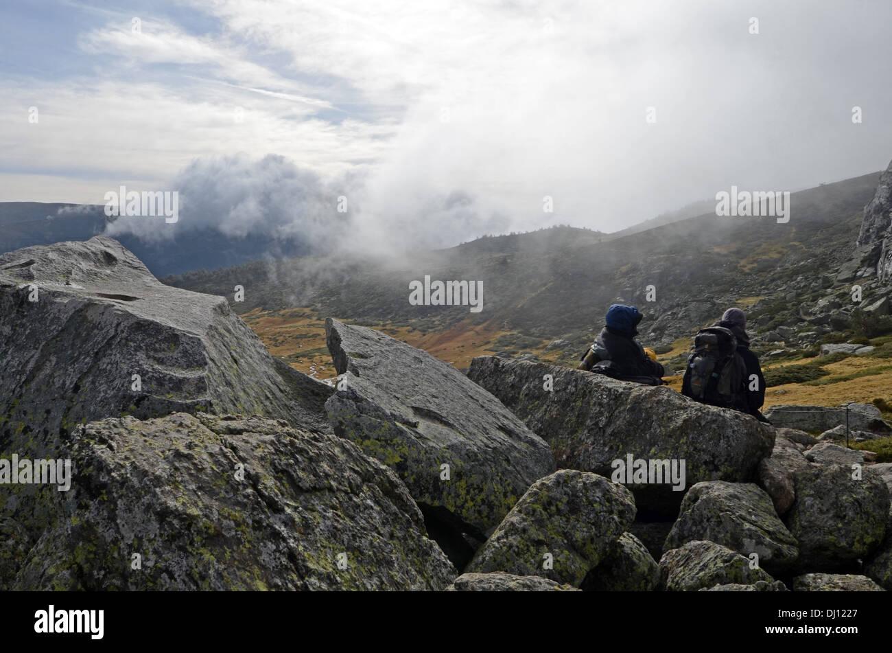 Hikers in Peñalara, highest mountain peak in the mountain range of Guadarrama, Spain Stock Photo