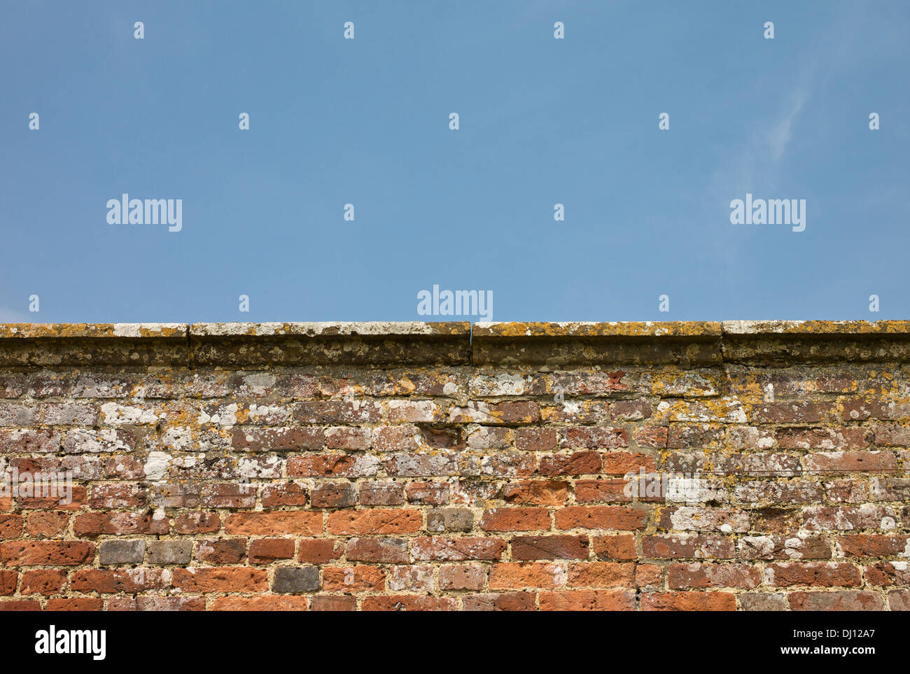 Aging and weathered brick wall and coping against blue sky. Stock Photo