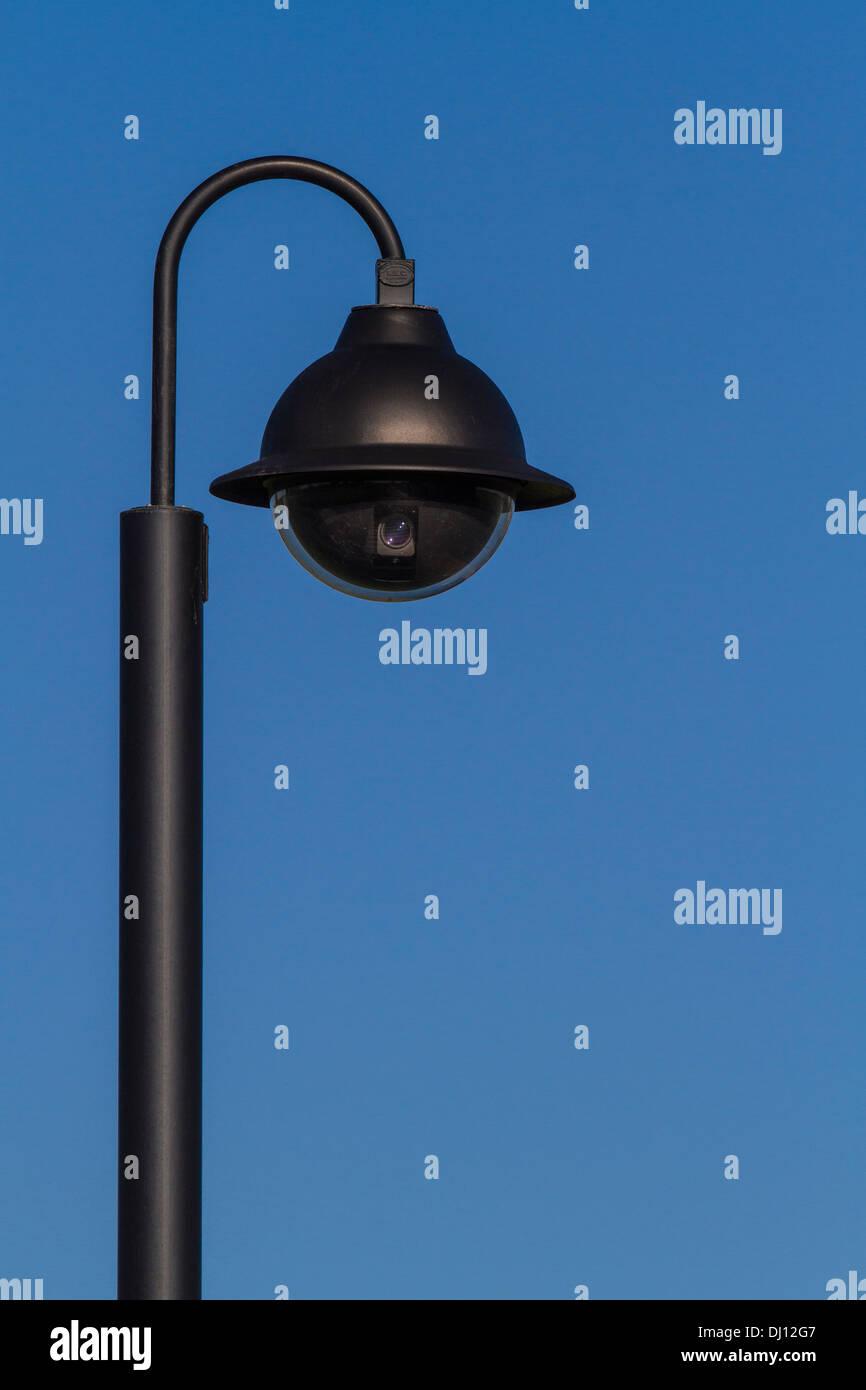 Globe-shaped surveillance camera against a blue sky - Stock Image