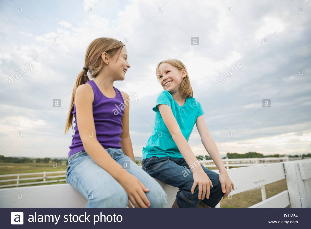 Smiling sisters sitting on railing looking at each other - Stock Image