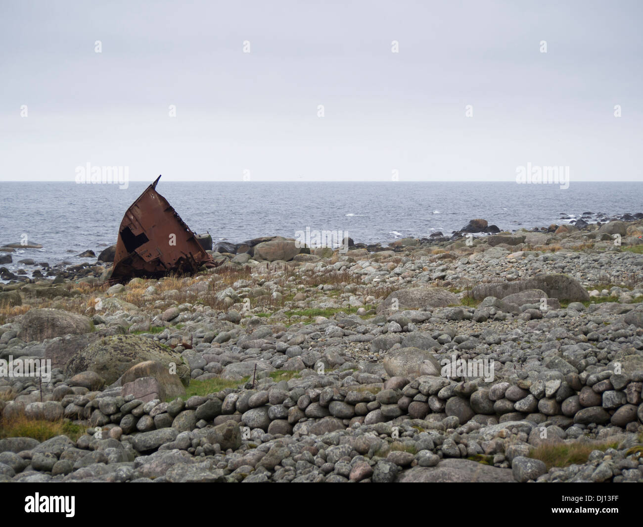 Rusty shipwreck on the shoreline of the North sea, Jæren near Stavanger Norway, rolling stones, stone wall and rough seas - Stock Image