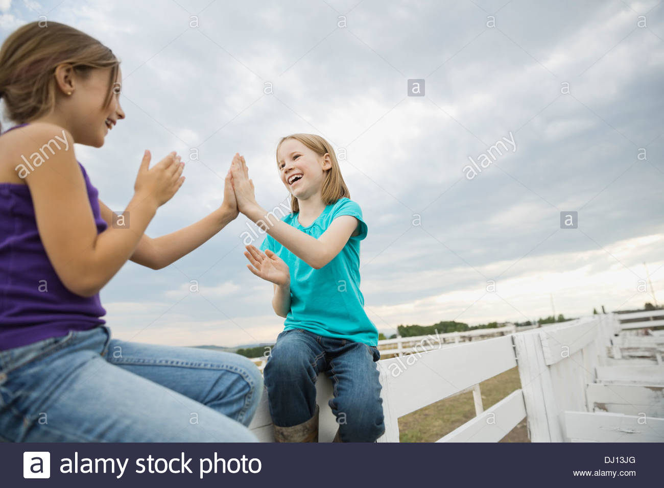 Smiling sisters sitting on fence outdoors - Stock Image