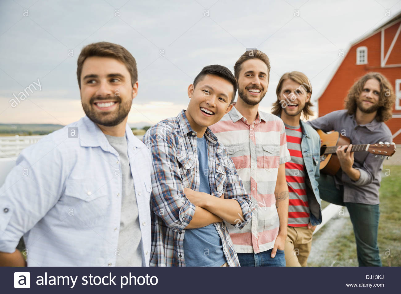 Group of male friends hanging out on a farm - Stock Image