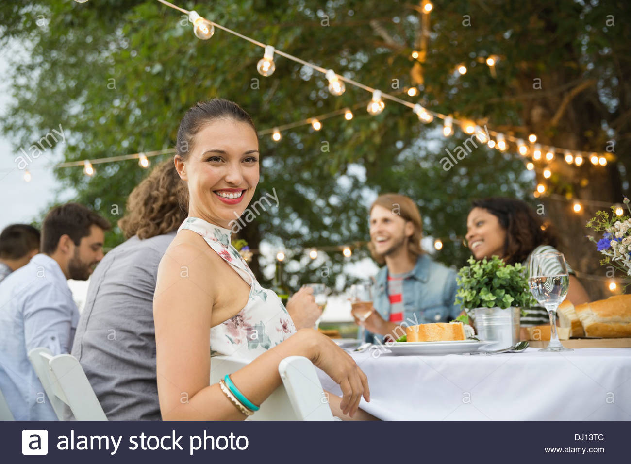 Smiling woman sitting with friends at outdoor dinner party - Stock Image