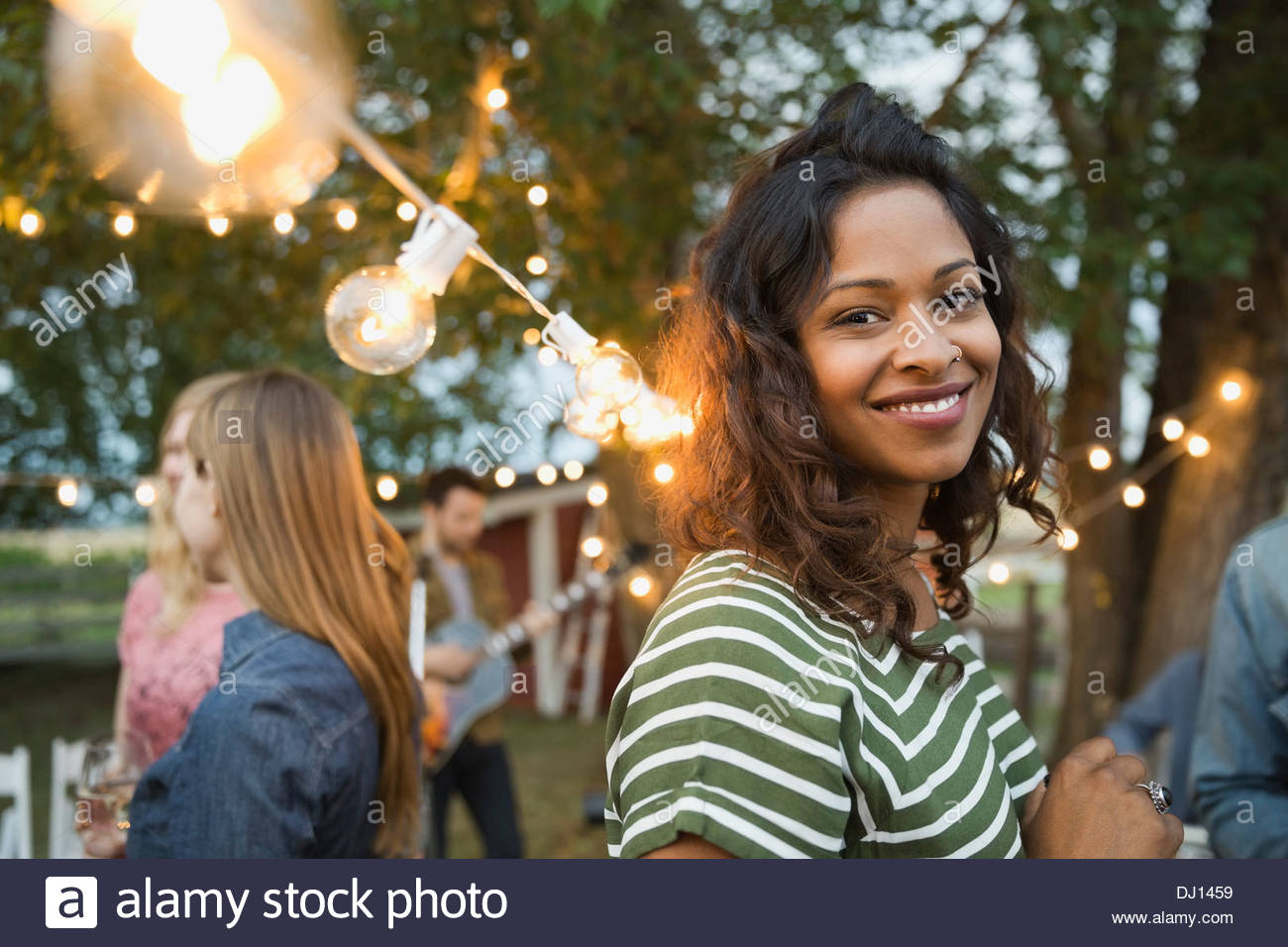 Portrait of smiling woman at outdoor party - Stock Image