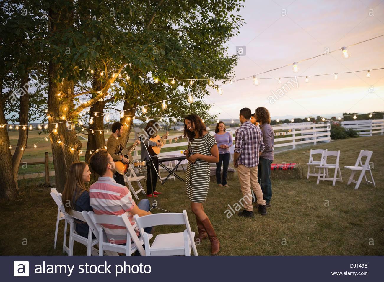 Friends enjoying outdoor farm party - Stock Image
