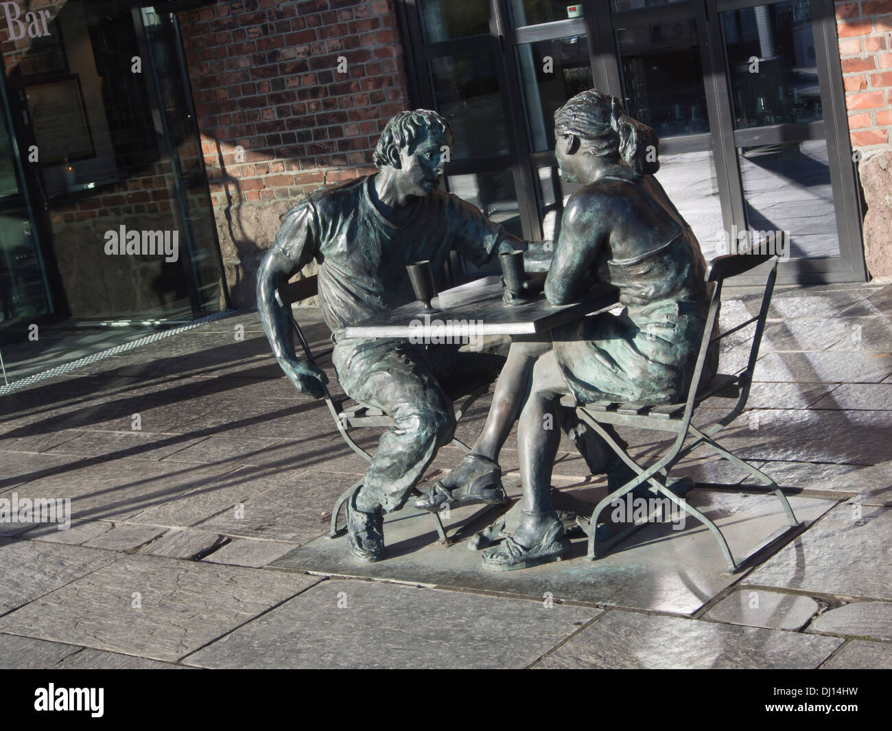 Sculpture of a young couple enjoying refreshments at an outdoor restaurant in Aker Brygge Oslo Norway, sculptor Per Ung - Stock Image