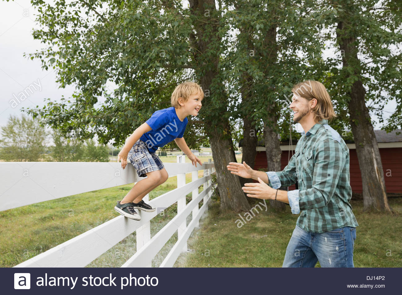 Playful son jumping off fence into fathers arms - Stock Image