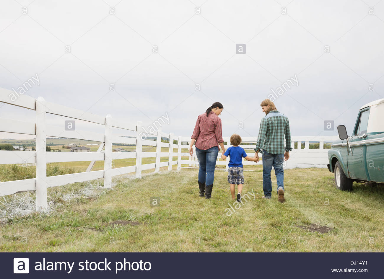 Family of three walking together on farm - Stock Image