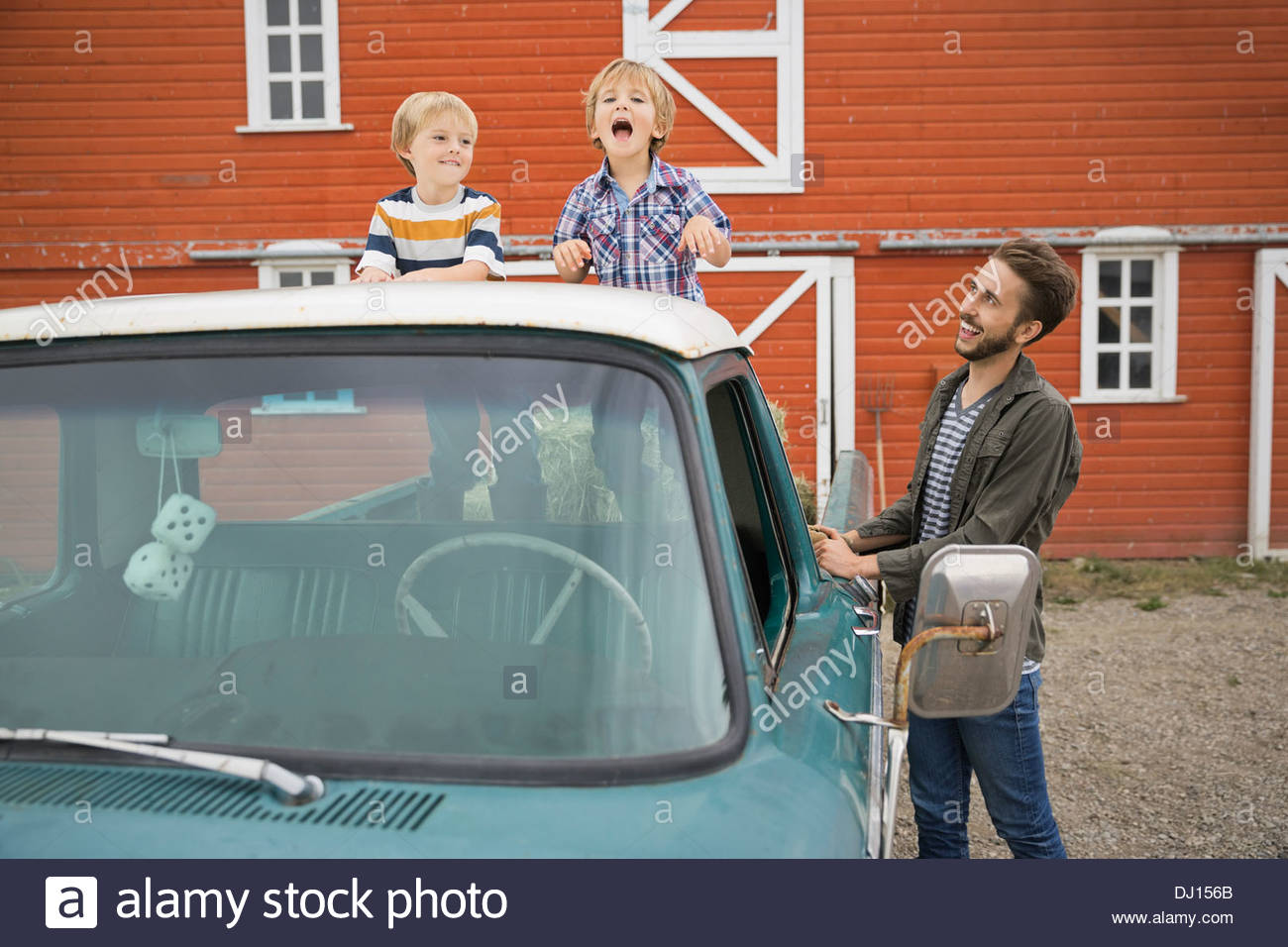 Man looking at children standing on pick-up truck - Stock Image