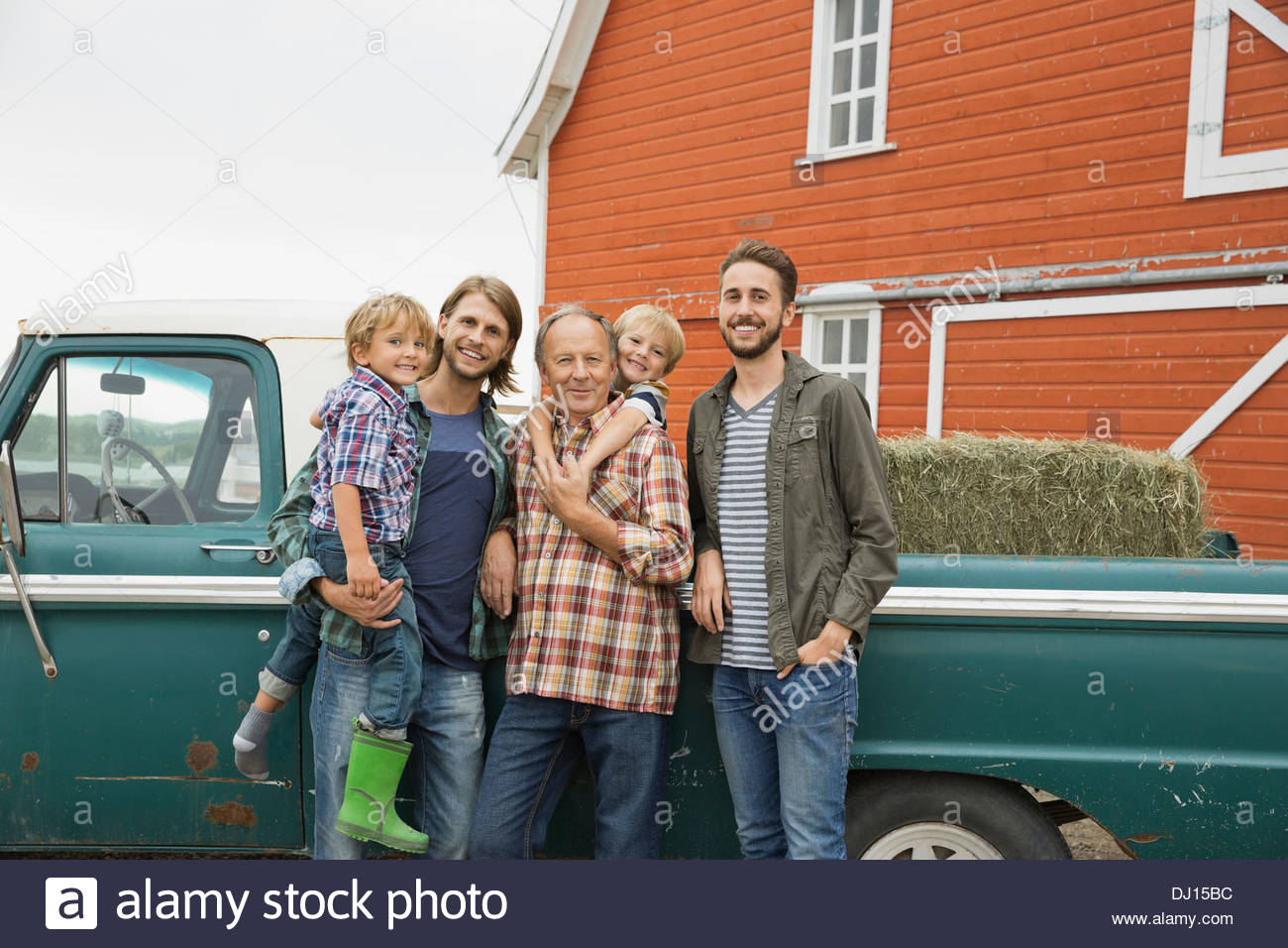 Happy three generation male family standing by pick-up truck - Stock Image