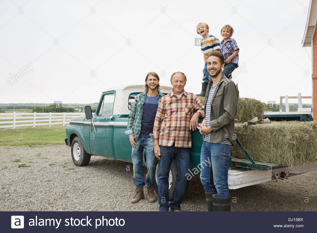 Three generation male family standing by pick-up truck - Stock Image